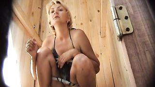 Blonde woman in bikini taking a leak in the beach WC--_short_preview.mp4